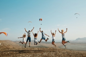 Friends joyfully jumping with glider in background