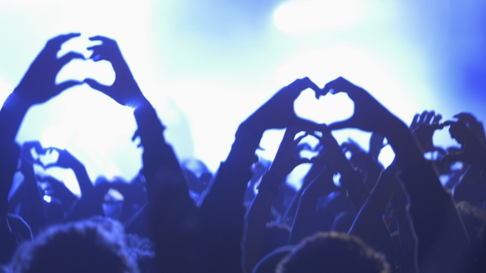 A concert crowd forming a heart with the hands at a life music concert, some visible noise due high ISO because of challenging lighting conditions, soft focus, some motion blur due movement